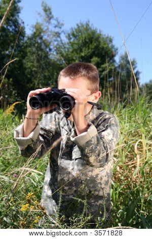 Joven en camuflaje en un campo mirando a través de binoculares