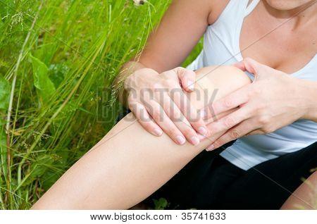 mujer joven con trauma de pie en el campo.