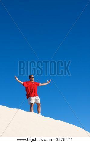 A Man Standing Atop A Sand Dune