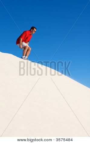 A Man Preparing To Jump Off Of Sand Dunes