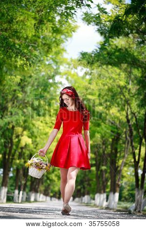 Beautiful girl enjoying in the spring time walking and holding basket full of flowers