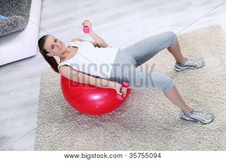 Exercise woman with lifting weights on ball in home living room