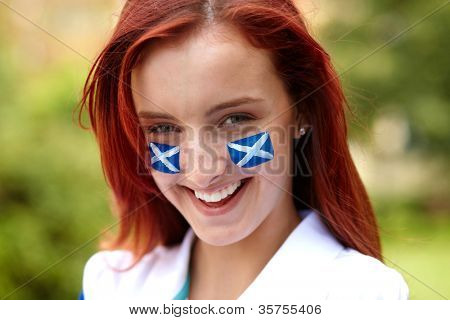 Happy female with Scottish flags on her cheeks, outdoor