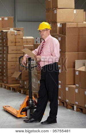 Senior manager check stock in the warehouse, wear yellow hardhat