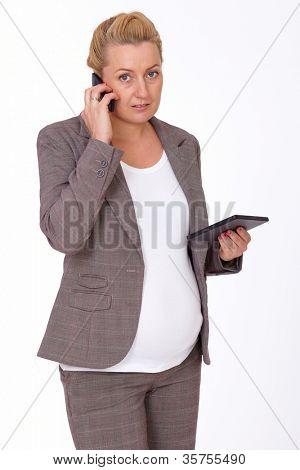 Attractive pregnant businesswoman over white background