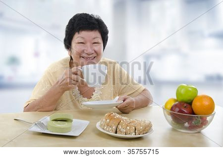 Asian senior woman having breakfast at home