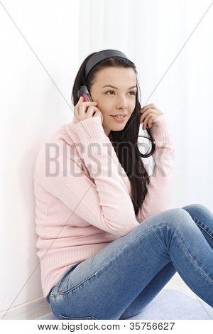Junge attraktive Frau sitzen auf Boden zu Hause, Gespräch am Mobiltelefon, Wegsehen.