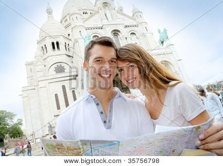 Couple in Montmartre reading tourist map