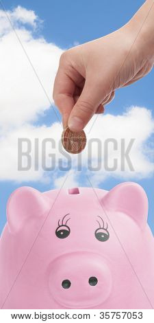 Pink pig money box with hand depositing British pound coin
