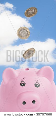 Falling British coins into pig money box against blue sky
