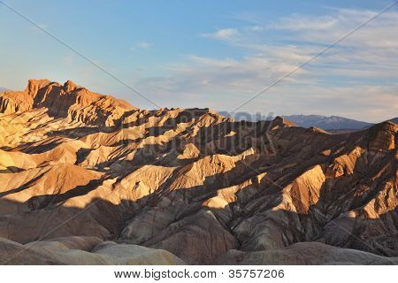 The famous section of Death Valley in California - Zabriskie Point. Picturesque hills of pink, yellow and chocolate hues. Sunset