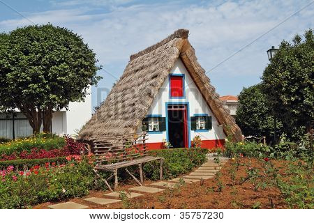 Classical triangular small house of the first settlers on island Madiera. A bright red door, a straw triangular roof, a small front garden and an accurate stone path