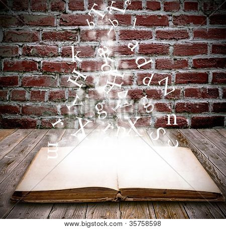 An open book with letters falling into the pages