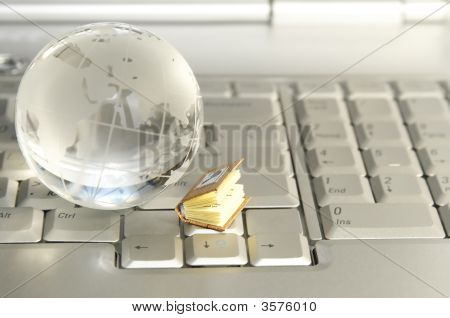 Little Book And Glass Globe On Laptop Keyboard
