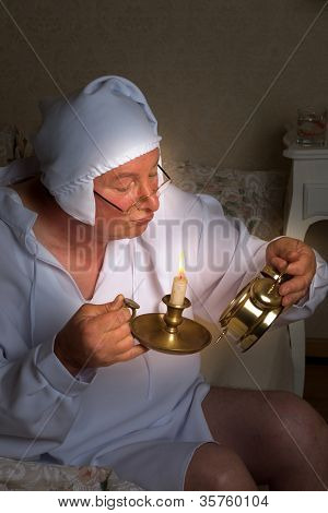Elder vintage man checking the time with a candle