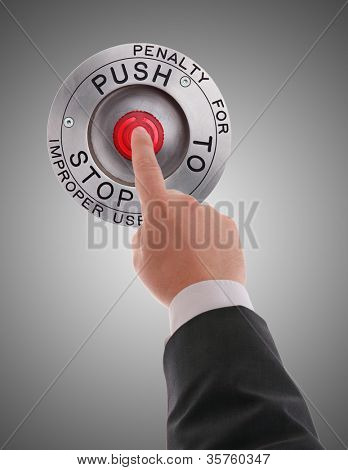 Red STOP button pressed by businessman's finger