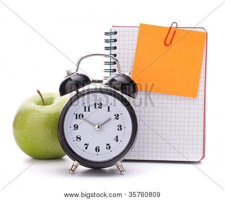Alarm clock, blank notebook sheet and apple. Schoolchild and student studies accessories. Back to school concept.