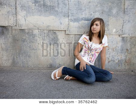 Outdoor photo of pretty teenage girl seated on pavement against grunge wall.