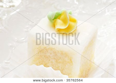 Elegant petit four with glaze frosting and yellow rose on decorative plate.  Macro with extremely shallow dof.