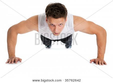 Young sport man, fitness muscle model guy making push ups exercise over  white background.