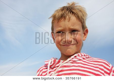 young child boy making faces over sky background