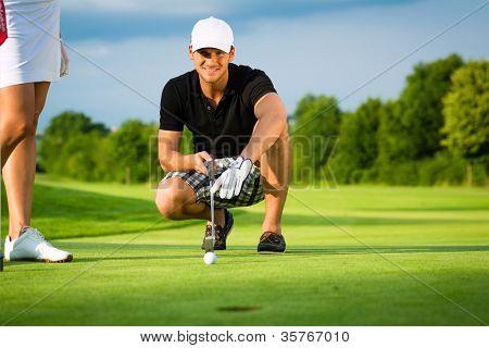 Junge Golfspieler auf dem Platz zu setzen, hat er mit dem Ziel, für seine Schuss