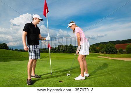 Jovem casal esportiva jogando golfe em um campo de golfe, ela está colocando no green