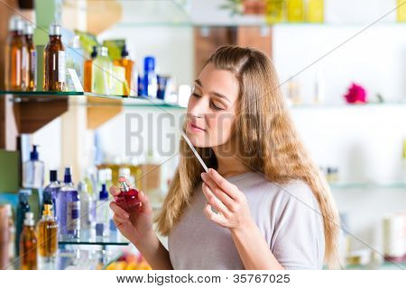 Young woman buying perfume in a shop or store, testing the fragrance with a paper tester