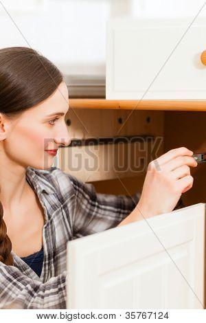 Junge Frau ist einen Schrank montieren, weil sie verschieben oder verkleinern
