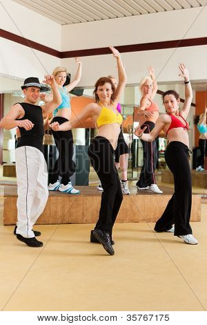 or Jazzdance - young people dancing in a studio or gym doing sports or practicing a dance number
