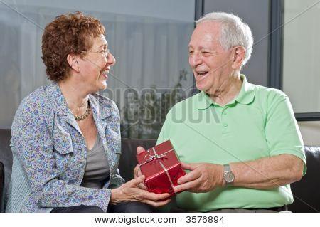 Senior Couple Giving Gift