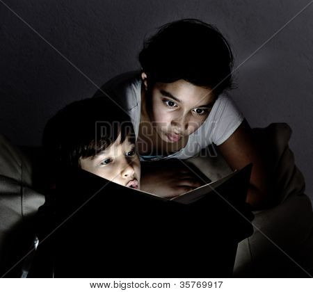 Cute kids reading a book at night