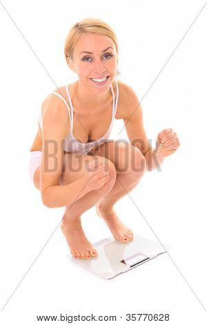 A picture of a young happy fit woman standing on a bathroom scales over white background