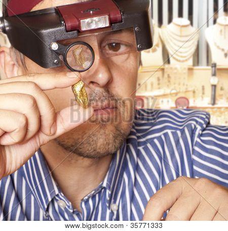 Un hombre que sostiene una joyería de la pepita de oro