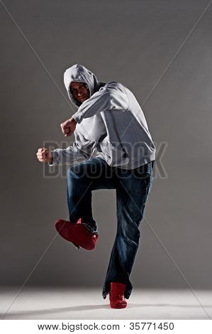 stylish dancer posing over grey background