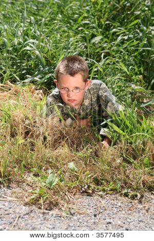 Young Child In Cammoflage Crawling Out Of The Grass