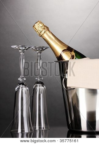 Champagne bottle in bucket with ice and glasses on grey background