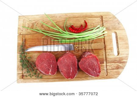 raw fillet chops : fresh beef meat with thyme and red hot dry pepper on wooden plate . isolated over white background