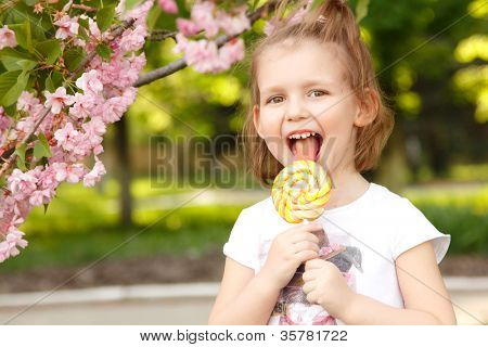 happy little girl licks sweet candy nature summer outdoor