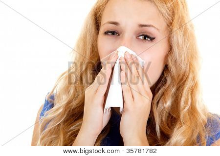 Young woman with cold sneezing into tissue over white background