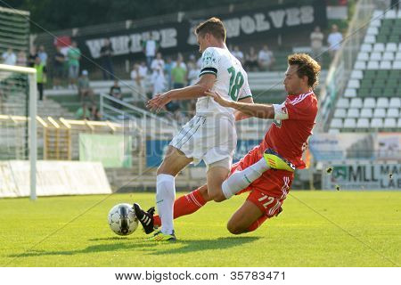 KAPOSVAR, HUNGARY - AUGUST 4: Benjamin Balazs (in white) in action at a Hungarian National Championship soccer game Kaposvar (white) vs Debrecen (red) August 4, 2012 in Kaposvar, Hungary.