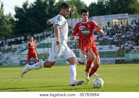 KAPOSVAR, HUNGARY - AUGUST 4: Bojan Pavlovic (in white) in action at a Hungarian National Championship soccer game Kaposvar (white) vs Debrecen (red) August 4, 2012 in Kaposvar, Hungary.