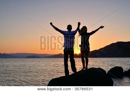 A girl with a guy raised his hands to the sky and watching the sunset at the beach