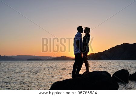 Man and woman in his arms against the sea and sunset