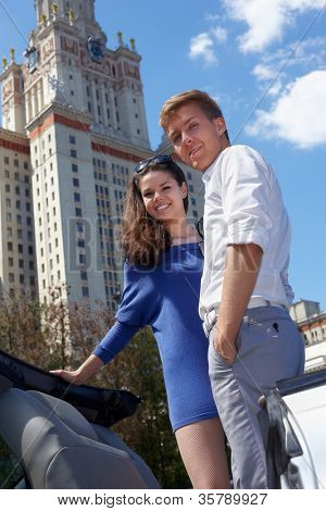 Young smiling couple stands on background of blue sky near to Lomonosov Moscow State University main building.