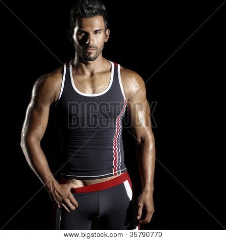 Very well built sexy male model in fashionable active sportwear against black background with copy space
