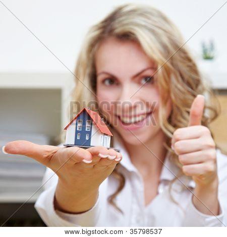 Mulher loira sorridente com casinha segurando seus polegares