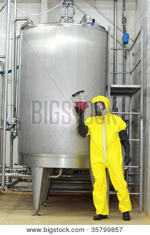Technician in yellow protective uniform,mask,goggles,gloves  examining sample of liquid at large industrial process tank in factory