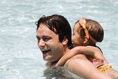 picture of swimming pool family  - Father playing with his daughter in swimming pool - JPG