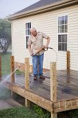 stock photo of pressure-wash  - Contractor pressure washing deck getting home ready to sell - JPG